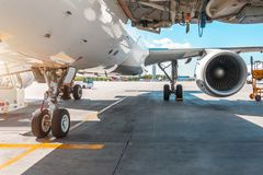 View of front chassis, wing and the big engine of the aircraft in the parking lot at the airport, the platform on a sunny day. View of front chassis, wing and Stock Photography