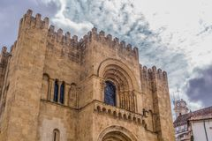 View of front facade of the medieval building of Coimbra Cathedral, Coimbra city and sky as background. Coimbra / Portugal - 04 04 2019 : View of front facade of royalty free stock images