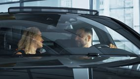 Happy family with kids in new car. View through front glass of happy kissing parents and chatting with content children sitting in new bought car in showroom stock image