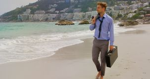 View of Front view of Caucasian Businessman walking with briefcase on the beach 4k. View of Front view of Caucasian Businessman walking with briefcase on the stock footage