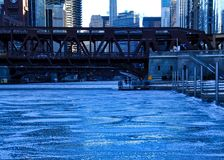 View of frozen Chicago River and riverwalk on a blue, frigid morning in winter. View of bridge crossing a frozen Chicago River and riverwalk on a blue, frigid stock photos