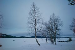 A view of frozen lake in Lapland. A view of frozen lake in Lapland, showing two chairs in the middle stock images