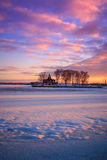 View of a frozen lake during sunrise in winter season. Stock Photos