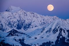 Full moon rising over a winter mountain landscape. View of a full moon rising over a winter mountain landscape in the Swiss Alps near Klosters royalty free stock photo