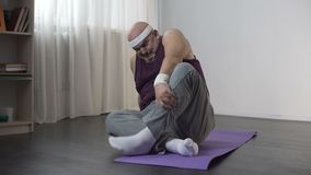 View of funny overweight man doing yoga at home, trying to sit in lotus pose. Stock footage stock video footage