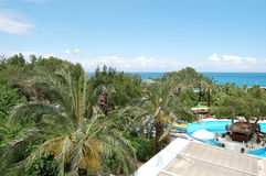 View of the garden, pool and the sea on the Mediterranean resort. A view of a green garden, a swimming pool, a poolside bar and blue sea in the hotel of high royalty free stock photos