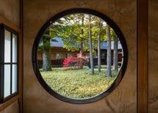 View of a Garden Through a Round Window Stock Photos