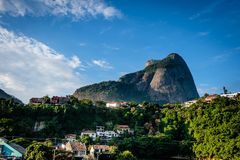 View of the Gavea Stone, seen from below with houses on the hill during late afternoon. Barra da Tijuca, Rio de Janeiro.  stock photos