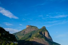 View of the Gavea Stone, seen from the street with houses on the hill during late afternoon. Barra da Tijuca, Rio de Janeiro.  stock images