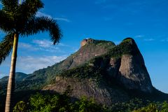 View of the Gavea Stone, seen from the street with houses on the hill during late afternoon. Barra da Tijuca, Rio de Janeiro.  royalty free stock photos