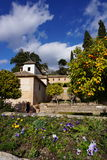 View in the Generalife Garden, Granada, Spain. Showing violet flowers in the foreground, some orange trees and an arabic residence to the left Royalty Free Stock Photo