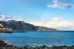View of Giardini Naxos town, cape and rainbow Stock Photo