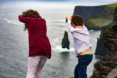 Girl and Boy pretending to dive off the Cliffs of Moher Tourist Attraction in Ireland. View of Girl and Boy pretending to dive off the Cliffs of Moher Tourist Royalty Free Stock Photography