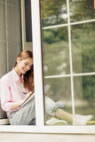 View of a girl in casual clothes sitting on window sill. Royalty Free Stock Photos