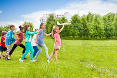 View of girl holding airplane toy and kids behind. View of girl holding white airplane toy and kids behind running in the field during summer day Royalty Free Stock Photo