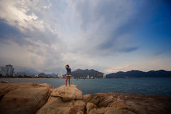 View of girl in short frock on rocks at distance against sea Royalty Free Stock Photo