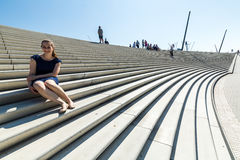 View of a girl sitting on the stairs at the Landungsbruecken in. A girl sitting on the stairs at the Landungsbruecken in Hamburg, Germany royalty free stock photo