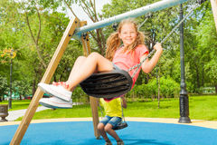 View of girl swinging and boy behind sitting Royalty Free Stock Photo