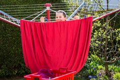 View of a girl working in the backyard. Girl is hanging the washed red sheets up in the garden Stock Photos