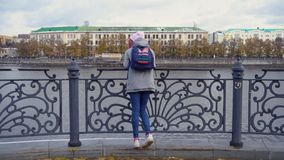 View of girls from back standing on pier. Young woman in warm clothes standing at steel railing of pier. Views of autumn stock photos