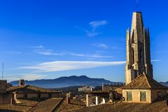 View of Collegiate Church of St. Felix spire and Puig de la Banya del Boc in the distance stock photos
