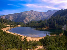View of glacial lake with some mountains in the background in national park Pirin. A view of glacial lake with some mountains in the background in national park stock photos