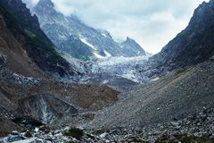 View of glacier and icefall. View of glacier, icefall and ice cave with high cliffs on background Stock Photo