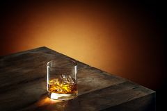 Whiskey. View of glas of  whiskey on wooden table on color background Royalty Free Stock Photo
