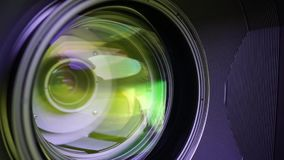 View of the glass elements in a camera lens. Objective under yellow light. Tilt-shift use. stock footage