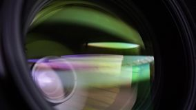 View of the glass elements in a camera lens. Objective under yellow light. Tilt-shift use. stock video footage