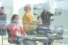 View through the glass wall. a group of fashion designers discussing new ideas.  royalty free stock photos
