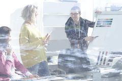 View through the glass wall. a group of fashion designers discussing new ideas.  stock images