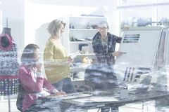 View through the glass wall. a group of fashion designers discussing new ideas.  royalty free stock image