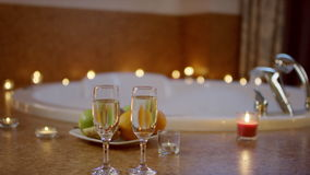 View of glasses of champagne and plate with fruits standing near jacuzzi in bathroom. stock footage