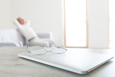 View of glasses lying on the modern laptop with resting man sitting on scandinavian design sofa Royalty Free Stock Photography