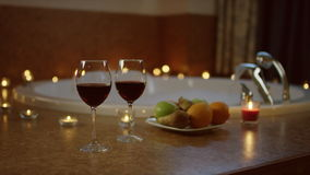 View of glasses of red wine and plate with fruits standing near jacuzzi,. View of glasses of red wine and plate with fruits standing in the bathroom. preparation stock video