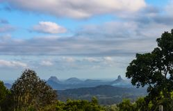 View of the Glasshouse Mountains in Queensland Australia framed by trees - under cloudy blue skies with a fire in the valley stock images