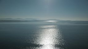 View of glistening and shimmering sea surface with hills on the horizon. Defocused glow of sun reflecting off sea water stock footage