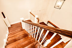 View of glossy wooden stairs from top showing the closed door Stock Image