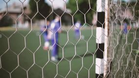 A view through the goal net. Four players in purple practice soccer drills in front of the goal in this stock video. The camera is looking through the net of the stock footage
