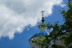 View on golden cross and russian orthodox church on blue sky and clouds background. Bolshaya Halan, Russia Stock Image
