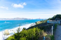 The view of golden gate bridge in Lands end at San Francisco- San Francisco. summer , cloud , rock , sea, plant. royalty free stock photography