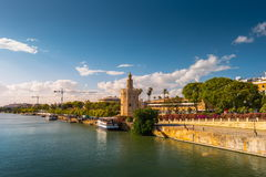 View of Golden Tower, Torre del Oro, of Seville, Andalusia, Spai. N over river Guadalquivir at sunset. Clouds over historic buildings stock image