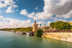 View of Golden Tower, Torre del Oro, of Seville, Andalusia, Spai. N over river Guadalquivir at sunset. Clouds over historic buildings royalty free stock photo
