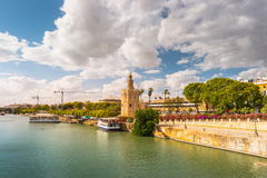 View of Golden Tower, Torre del Oro, of Seville, Andalusia, Spain. Over river Guadalquivir at sunset. Clouds over historic buildings royalty free stock photos
