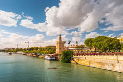 View of Golden Tower, Torre del Oro, of Seville, Andalusia, Spai. N over river Guadalquivir at sunset. Clouds over historic buildings royalty free stock images