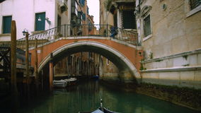 View from a gondola in canal. View from a gondola as it glides under a bridge in canal stock footage