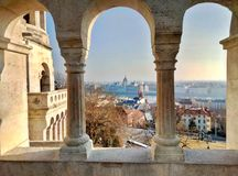 View on the gothic parliament of Budapest through the columns of the Fisherman`s Bastion stock photography