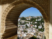 View of Granada through Islamic arch at the Nazarene Palaces, Alhambra, Granada Royalty Free Stock Photos