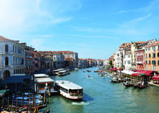 View of Grand Canal from Rialto bridge with vaporettos full of tourists and gondolas in a sunny day, Venice, Italy Royalty Free Stock Photo